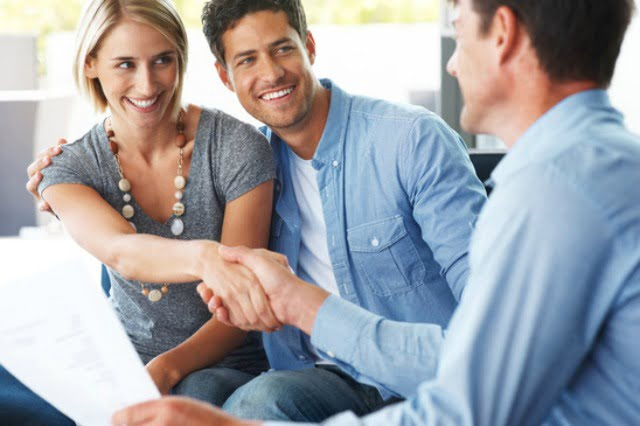 Portrait of a happy young couple shaking hand with financial advisor at home